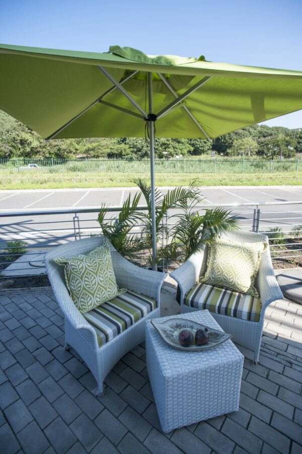 Makuti armchairs with stripped green cushions.